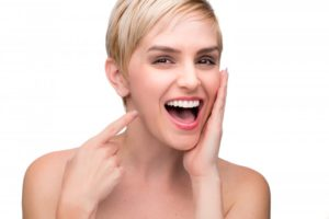 woman smiling pointing at perfect teeth