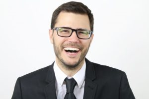 man in black suit laughing