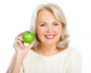 woman smiling holding green apple