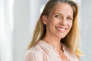 Smiling woman, confident that dental implants are worth the cost